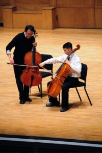 Image of Yo Yo Ma with a student, both playing cellos on stage.